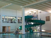 indoor pool with waterslide at end
